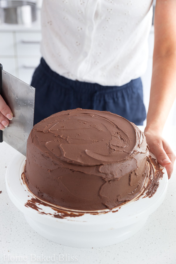 A woman using a benchscraper to smooth out the chocolate frosting.