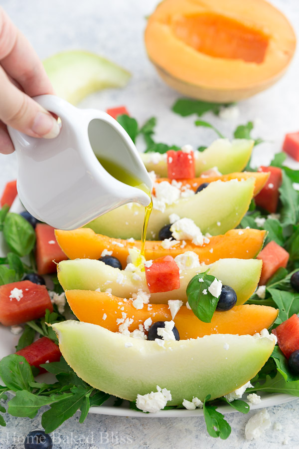 Olive oil being poured over the melon salad.