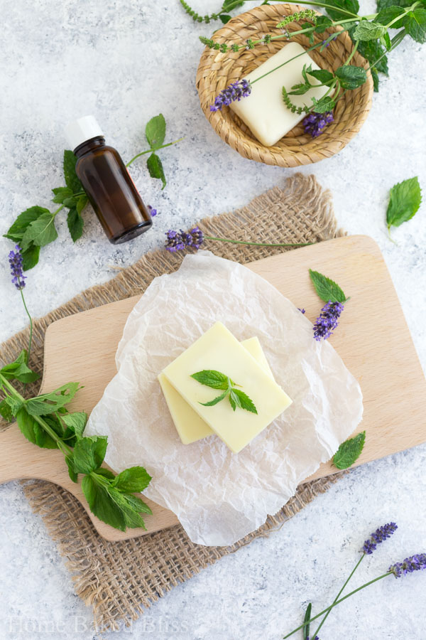 Peppermint Lotion Bars on a wooden board beside fresh mint and lavender.