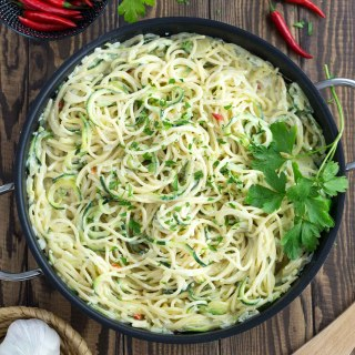 A pan with creamy zucchini noodles next to a bowl of red chilis.