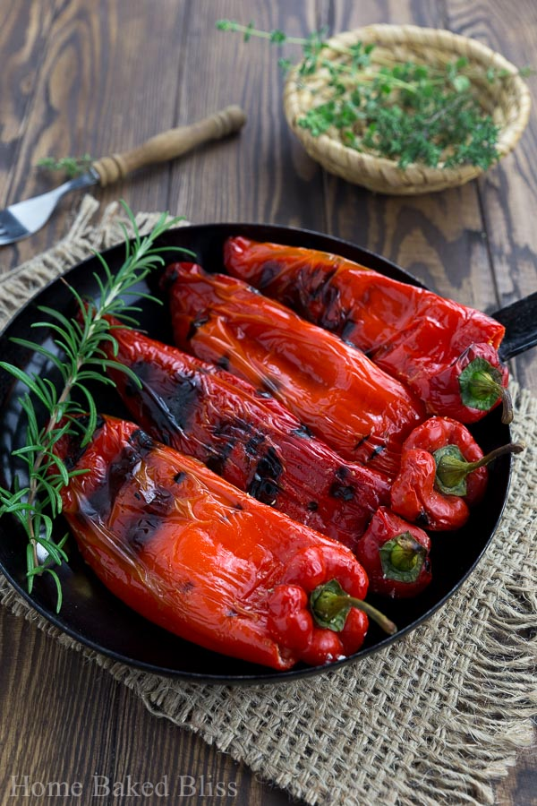 Grilled Peppers with Feta in a black pan with a twig of rosemary