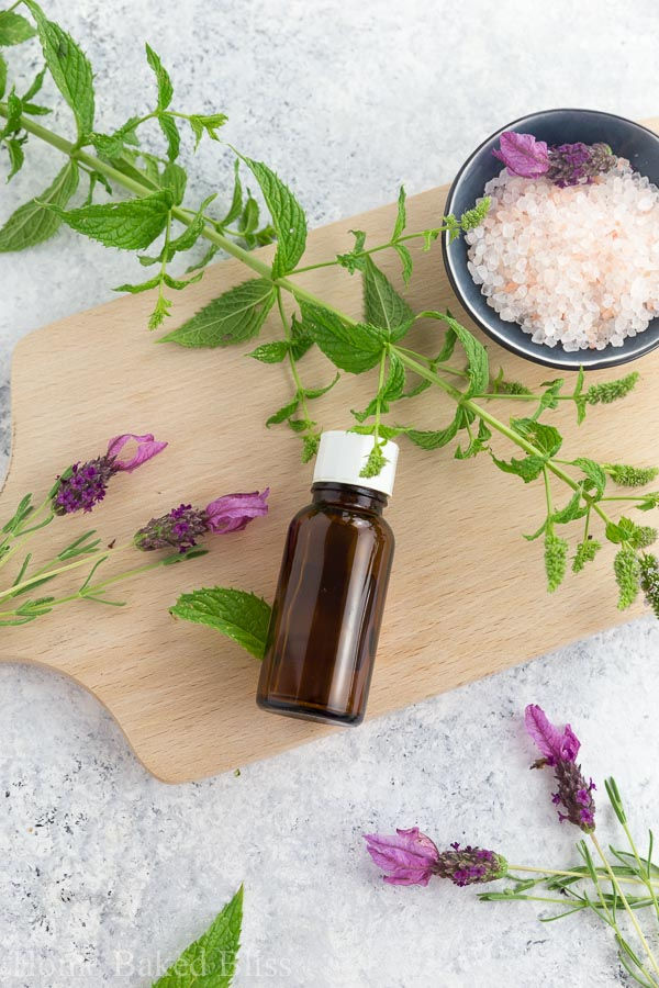 A brown bottle of peppermint essential oil on a wooden board.