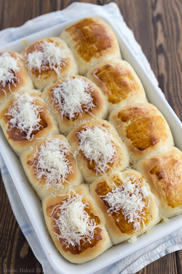 Sprinkling parmesan onto the garlic dinner rolls.
