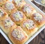 Garlic parmesan dinner rolls inside a white casserole pan.