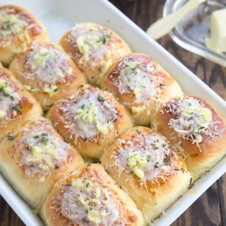 Garlic parmesan dinner rolls inside a white casserole pan.