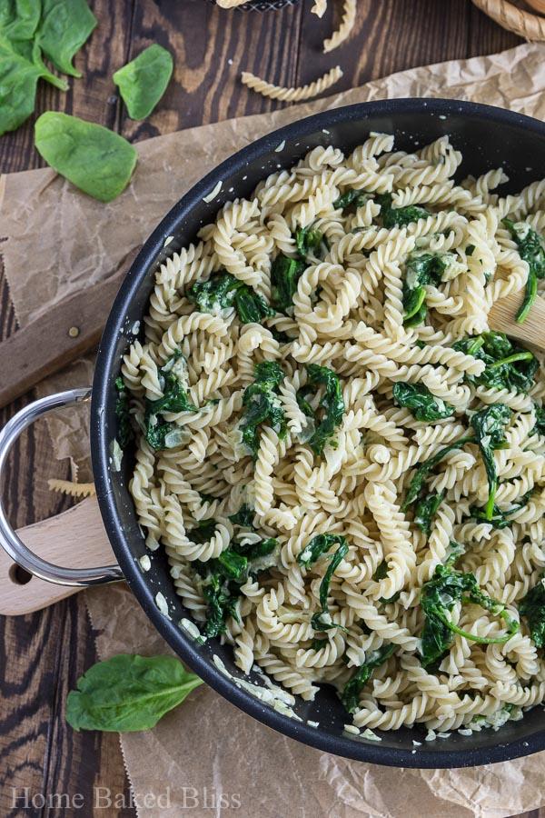 Spinach noodles inside a black skillet.