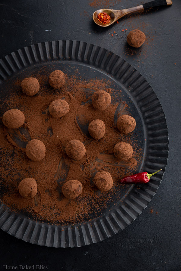 Spicy chili truffles rolled in cocoa powder on a black plate.