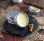 Cinnamon Cocoa Lip Balm in a small metal container beside a cinnamon stick.