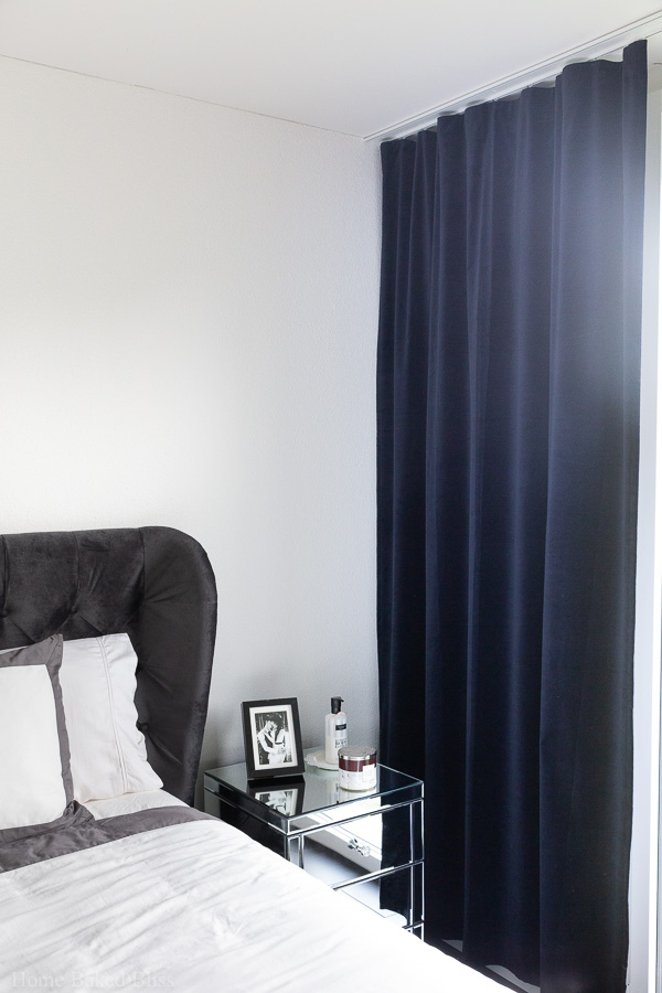 Blue velvet curtains next to a mirror night stand.