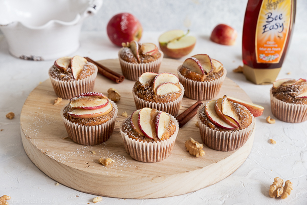 Apples walnut muffins next to tube of honey sprinkled with powedered sugar and garnished with apple slices