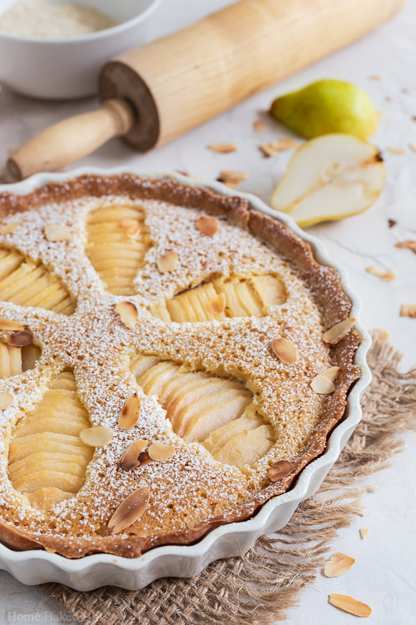 Closeup of Pear Frangipane Tart sprinkled with powdered sugar and garnished with toasted sliced almonds