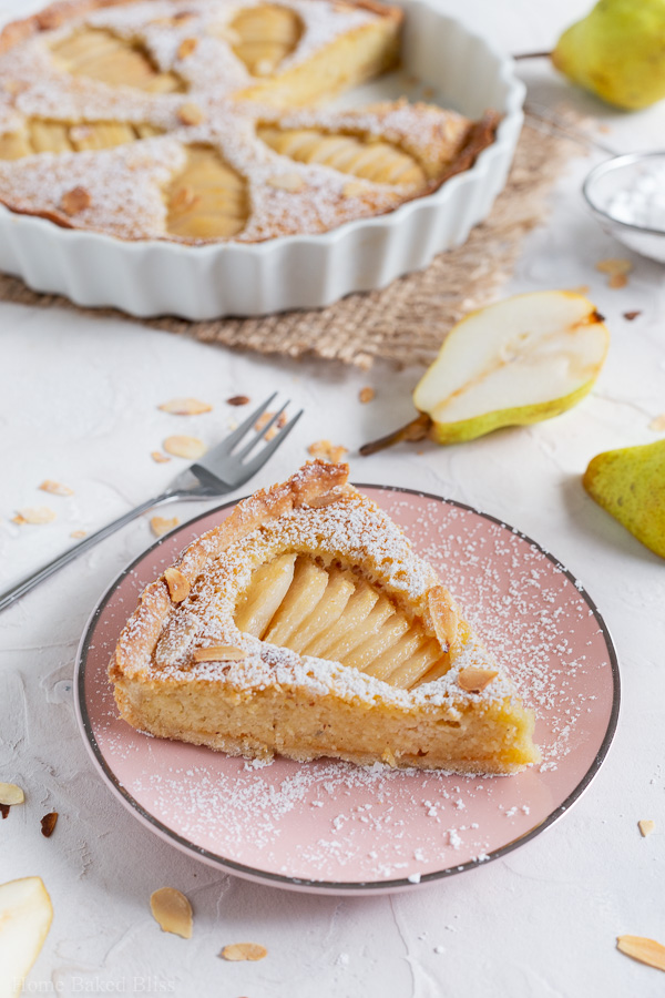 A slice of Pear Frangipane Tart sprinkled with powdered sugar and garnished with toasted sliced almonds on a pink plate
