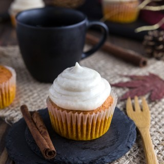 A pumpkin spice cupcake with cinnamon frosting next to a wooden fork.
