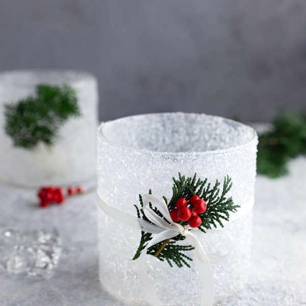DIY frosted candle jar with epsom salt, decorated with holly and white ribbon