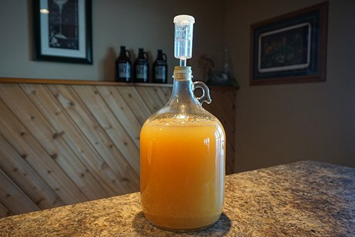 one gallon of cyser in a glass carboy with an airlock fitted on top