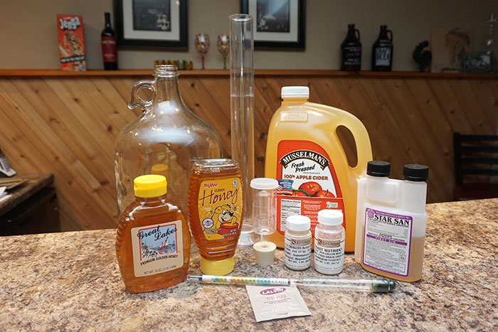 a gallon of apple cider, honey and equipment for making a Cyser