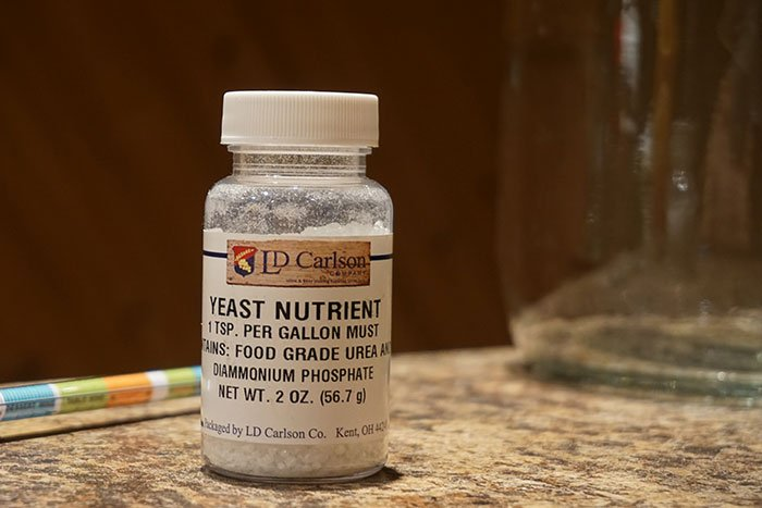 a small bottle of yeast nutrient with brewing instruments in the background