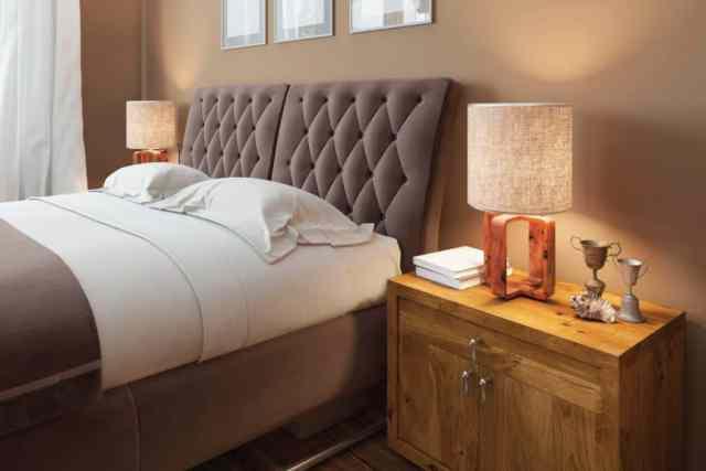 Modern bir yatak odasında etkileyici dokulara sahip ahşap komodinler