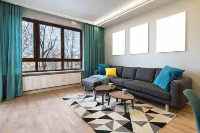Arka planda pencereler, duvarda koyu gri bir kanepe ve üzerinde mavi atma yastıkları olan muhteşem bir çağdaş oturma odası