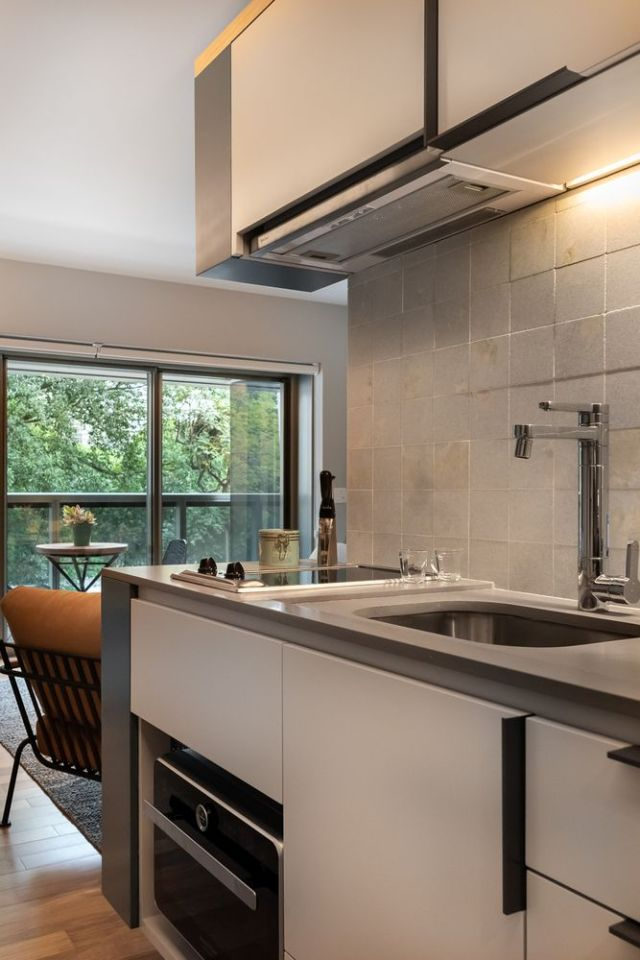 The kitchen is pretty small, there are white sleek cabinets, a neutral tile backsplash and additional lights