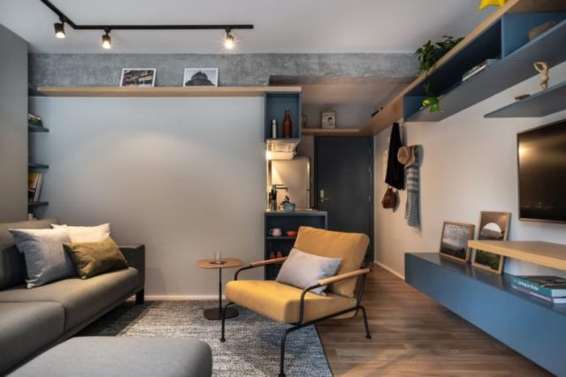 The living room is done in blue and greys, with upholstered and leather furniture, with lights and a home office space