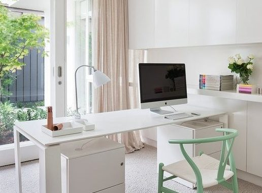 A Chic Neutral Home Office With A White Storage Unit That Takes The Whole Wall, A Desk And A Mint Chair
