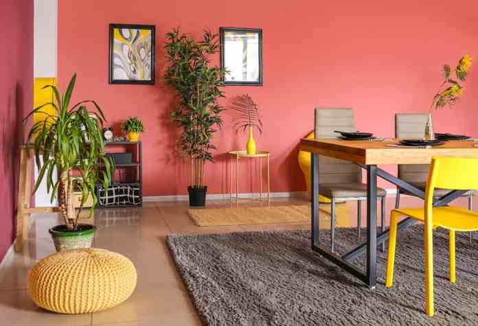 The pink walls have a small bit of earthiness to it that binds the rest of the colors in this quirky and informal dining room. The yellow elements stand out especially next to the gray hues of the area rug. The wooden elements also serve the same purpose.