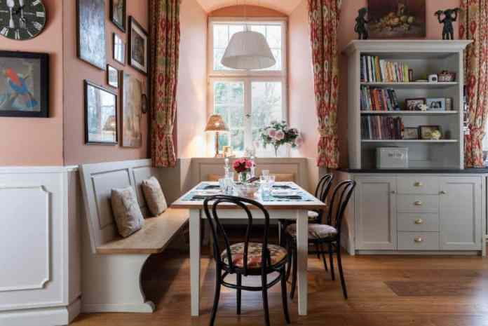 There is a homey warmth to this dining area that is enhanced by the floral curtains matching with the sit cushions of the black bamboo chairs paired with the wooden dining table. This is matched with an L-shaped wooden built-in bench.
