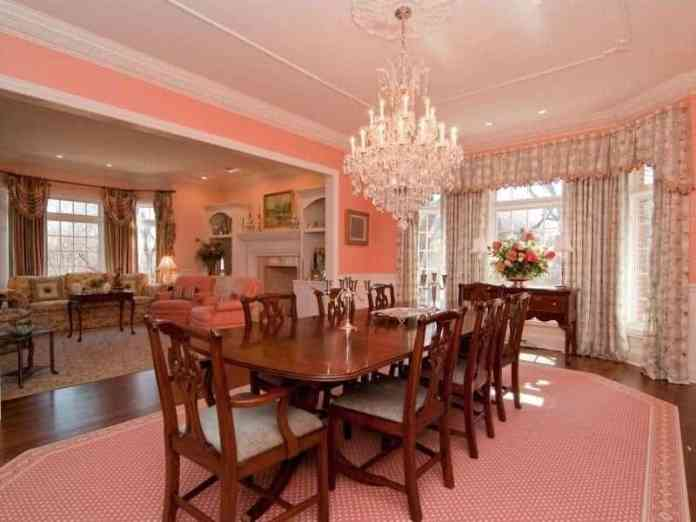 The pink patterned area rug that covers most of the dark hardwood flooring matches the pink walls and complements the beautiful chic curtains of the French windows that brighten up the majestic white crystal chandelier.