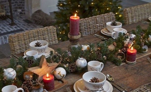 A Chic Winter Table Setting With An Evergreen, Lights And Pinecones Runner Plus Wooden Stars And Ornaments, Pillar Candles And Pinecones In Bowls