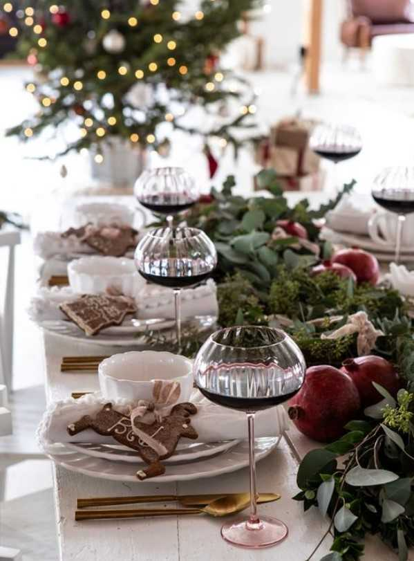 A Lush Winter Tablescape With A Greenery Runner With Pomegranates, Gingerbread Bcookies And Elegant Cutlery