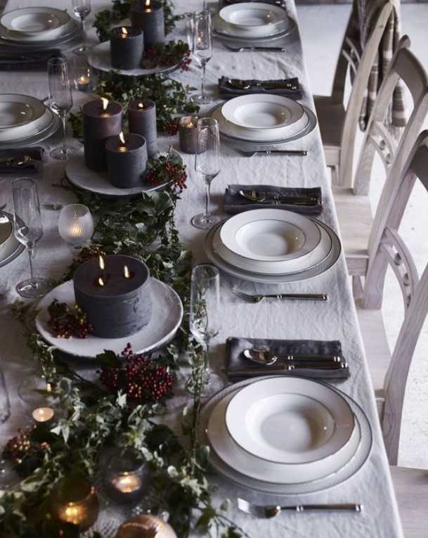 Dark Tone Winter Tablescape With Dark Candles, Greenery, Berries, Grey Napkins And White Porcelain