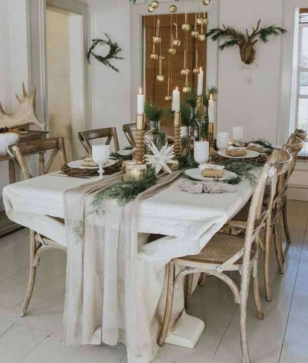 Neutral Winter Tablescape With A Neutral Runner, Greenery, Paper Stars Candles In Various Candleholders And Ornaments Hanging Over The Table