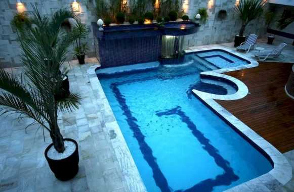 L Shaped Swimming Pool With Waterfall In A Backyard Courtyard