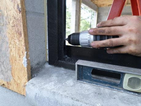 Drilling into the provided hole on the window frame, through the wood window buck and into the solid-poured concrete block cell with a puff of dust