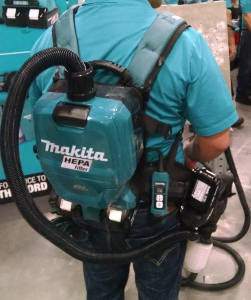 worker with backpack vacuum attached to small rotary hammer