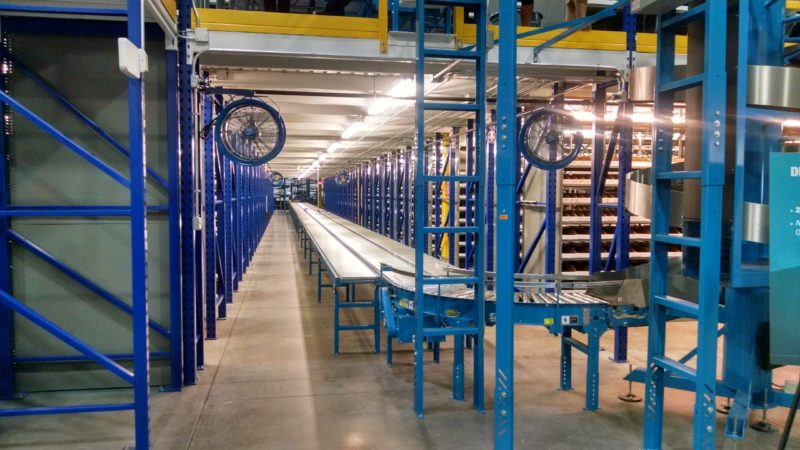 Storage and packing area with conveyor for rolling boxes along