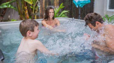 Foto van een gezin in een spa van Fantasy. Op de foto is te zien hoe een jongetje zijn vader nat spettert. Op de achtergrond lacht zijn moeder erom.