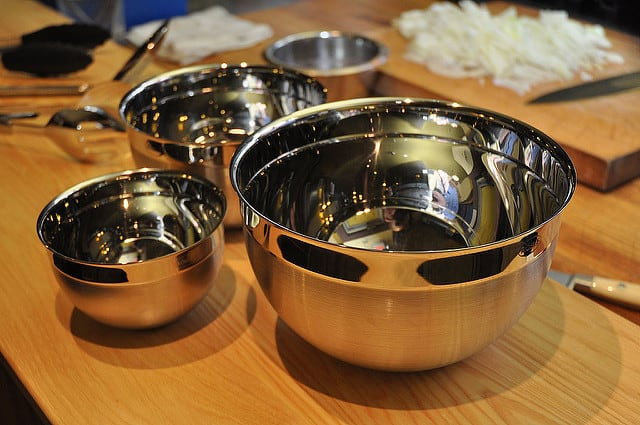 4 Stainless Steel Mixing bowls on a countertop, with chopped onions in background