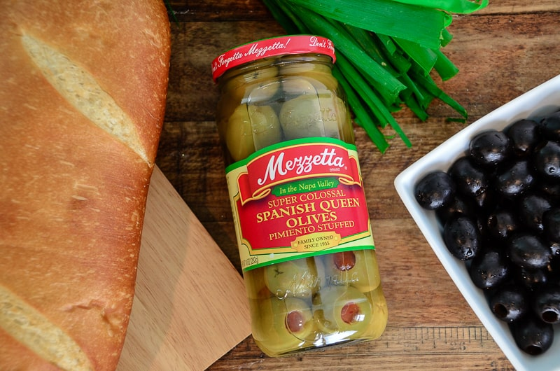 A jar of Spanish Olives lying on a wood table, surrounded by french bread, green onions, and black olives.