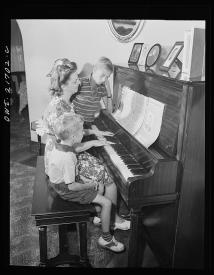 Howard and Earl Babcock enjoy singing to their mother's piano accompaniment