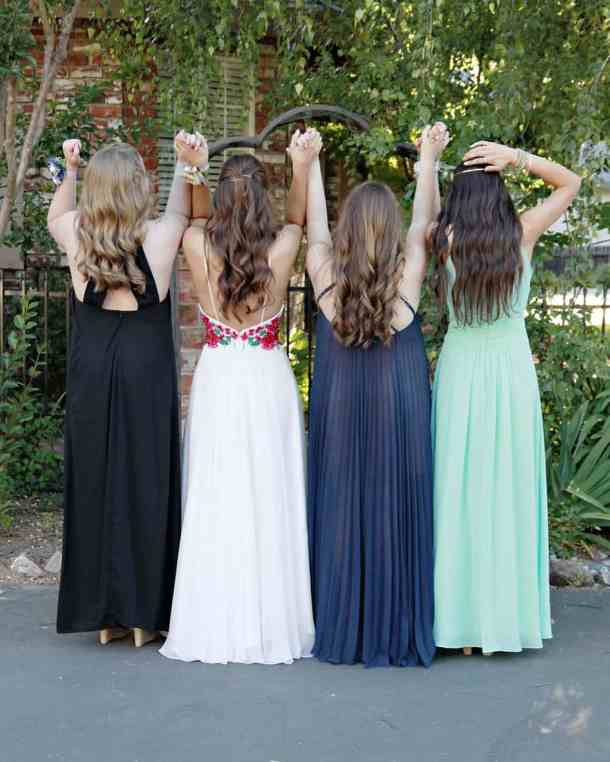 7a3cfb40afbf 4 girls in prom gowns facing away from camera holding hands