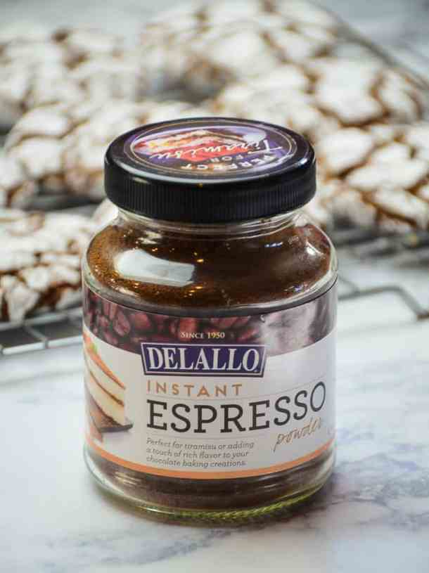 Jar of Delallo Espresso powder with Chocolate Crinkle Cookies in the background.