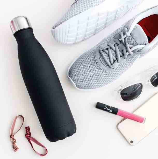 Water bottle, lip gloss, hair ties, sneakers and sun glasses laid out on a white surface