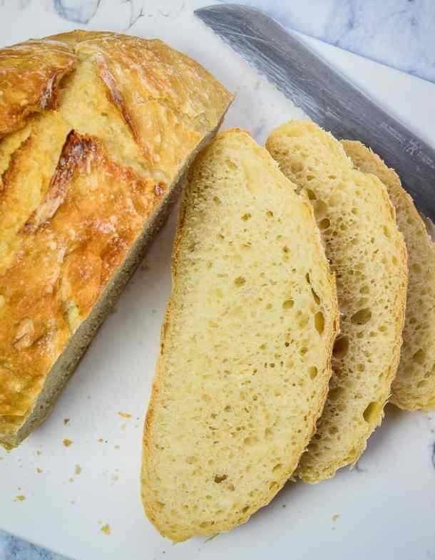 Sliced Crusty No Knead bread on a cutting board with bread knife.