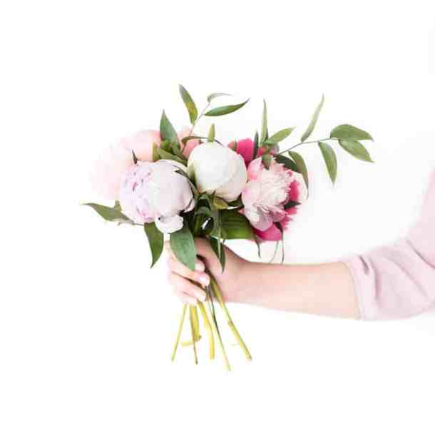 Bouquet of various varieties of peonies held in a womans hand.