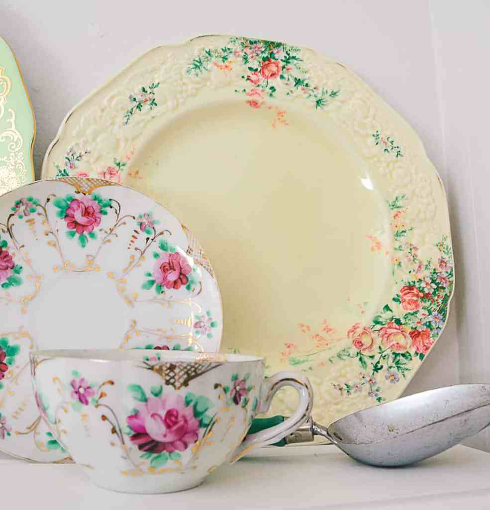 Large vintage dinnerplate with floral pattern on a white shelf, with a withe teacup with a rose pattern and vintage measuing scoop.