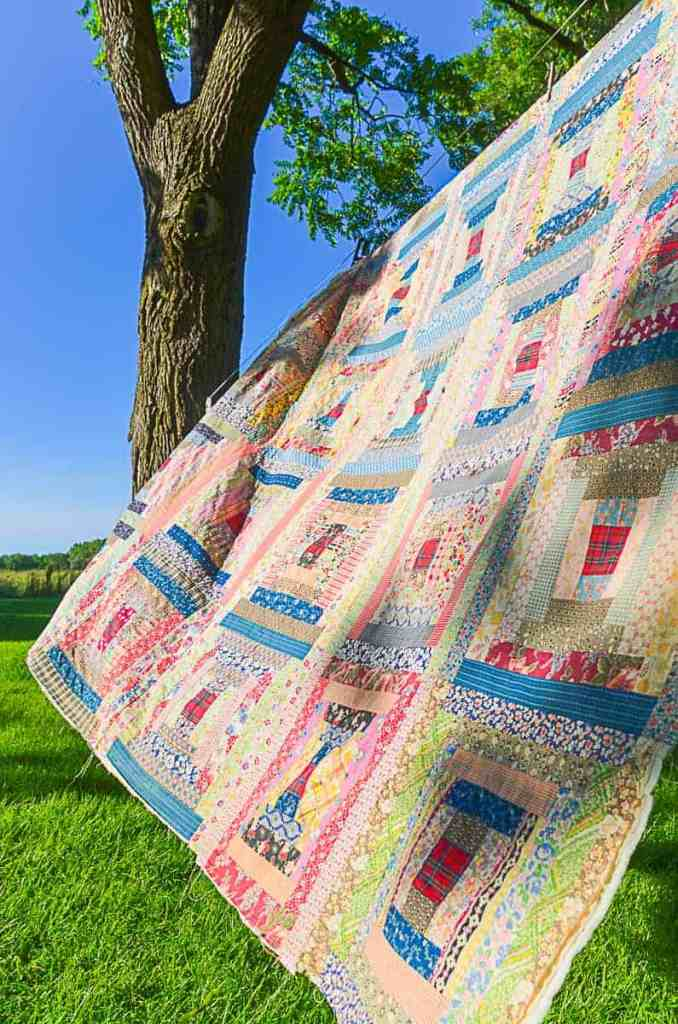 A log cabin quilt  hanging outdoors of a clothesline with blue skies in the background, the quilt top is made from vintage feedsack fabric.