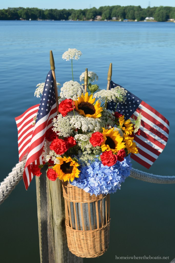 Basket on dock filled with flags, Queen Anne's Lace, hydrangeas, carnations and sunflowers! | ©homeiswheretheboatis.net #patriotic #july4th #flagday #LakeNorman