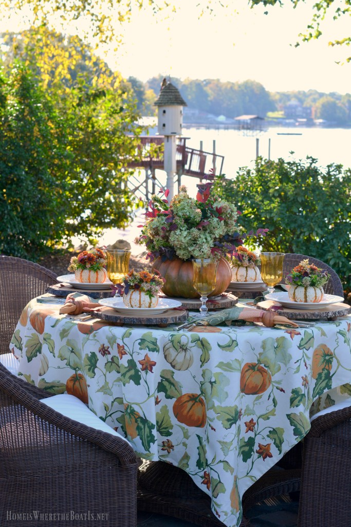 An Alfresco Fall Table with Blooming Pumpkins | ©homeiswheretheboatis.net #fall #tablescapes #pumpkinvase #lake #alfresco #DIY